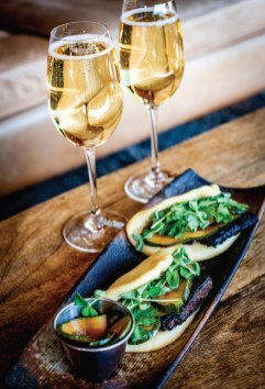 Char Sui Pork Belly with steamted bao buns, sriracha mayonnaise, spiced cucumber, and pea shoots, complemented by champagne.