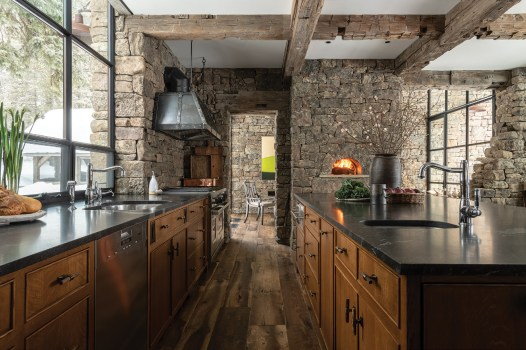 The kitchen features a wood-burning pizza oven, distressed white oak cabinetry, honed granite countertops, and a custom iron range hood by the Jackson Hole-based Heart Four Ironworks.