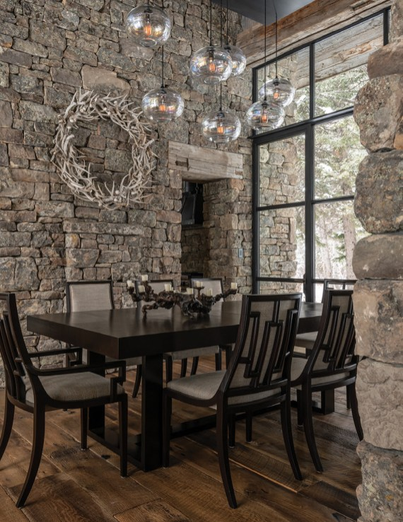 An antler wreath from Game Trail Gatherings, made by local artist Kyle Anderson, hangs on the stone walls of the dining room. The lighting is by John Pomp Studios, and the table and chairs are from Michael Berman Limited.