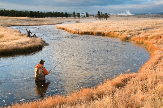 """In early October, at approximately 7:45 a.m., Dave Pearson explores the lower reaches of Nez Perce Creek in Yellowstone National Park. """"I love the warm, orangish sunrise light, and how it works with the angler's orange jacket,"""" Juracek says. """"I also like the shape of the river, and how the warm light contrasts with the cool light of the heavily overcast sky."""""""