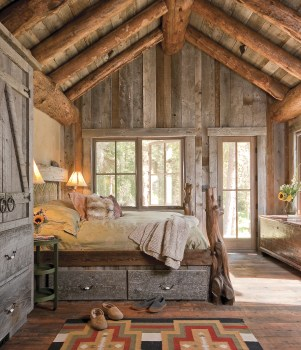 Custom built-in drawers ass efficiency to the master bedroom, while old barnwood walls and a steeply pitched ceiling give the room a cabin-like feel. The door on the far wall leads to a small creek that flows through the property.