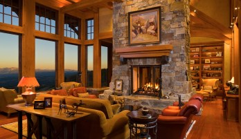 In the great room, reclaimed timbers and the masonry of the central fireplace are focal points in the room as much as the vistas toward the east.