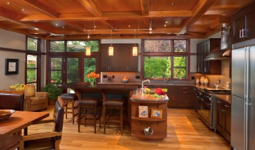 The contemporary kitchen, with cabinets by McPhie Cabinetry borders the large dining room table.