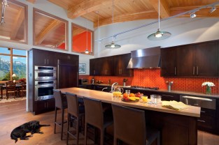 The kitchen bar accommodates informal meals while the tangerine tile backsplash converses with the dining room beyond. The detailing is clean, yet warm.