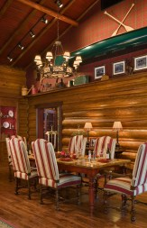 Utilizing lighting, bold upholsetry and the elegant lines of the furnishings, Warren Sheets Designs delineates the dining area from the open floorplan of the cabin.