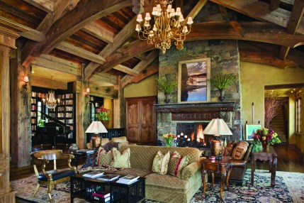 Incorporating luxurious upholstered furnishings, rugs and antiques adds an element of eclectic refinement to the rustic materials in the great room.