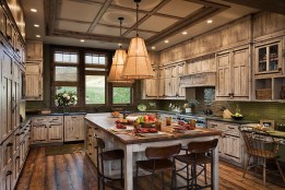 CenterMark Industries utilized reclaimed fir in the custom-built kitchen cabinetry. The cabinets are painted antique white, hand-distressed, then finished with a glaze and metal strap hinges.