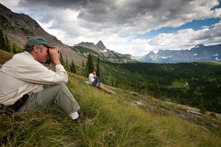Douglas H. Chadwick (left) and son Russell Chadwick look for grizzlies in Bear Valley while taking a break from hiking the Hi-Line trail near the Continental Divide in Glacier National Park, Montana. Photo by Ian Shive, Tandem