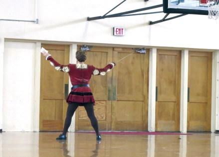 The antiquated gym at Willson School provides the chorus' dressing room and backstage area, where performers often play Frisbee between scenes. Here Melina Pyron, who played Stefano in Roméo et Juliette, practices her aria and swordplay. | Photo by Carter Walker