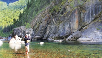 The author reels in a trout on the Upper Middle Fork of the Flathead River in the Great Bear Wilderness, one of the most pristine stretches of designated Wild and Scenic Rivers in North America. photo by Darwon Stoneman