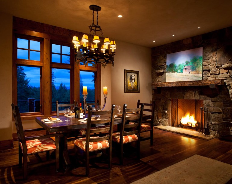 The fireplace and a touch of color on the seat cushions bring the dining room to life.