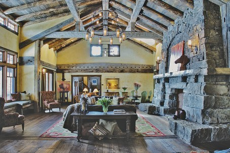 In this great room, hand-applied plaster in a lighter parchment color offsets the rustic elements of antique timbers and stacked stone.