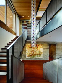 """A Venini chandelier nearly two stories high hangs in the stairway between the main floor and guest quarters. """"We knew this was part of the art program and designed an appropriate space for it,"""" says architect Eric Logan."""
