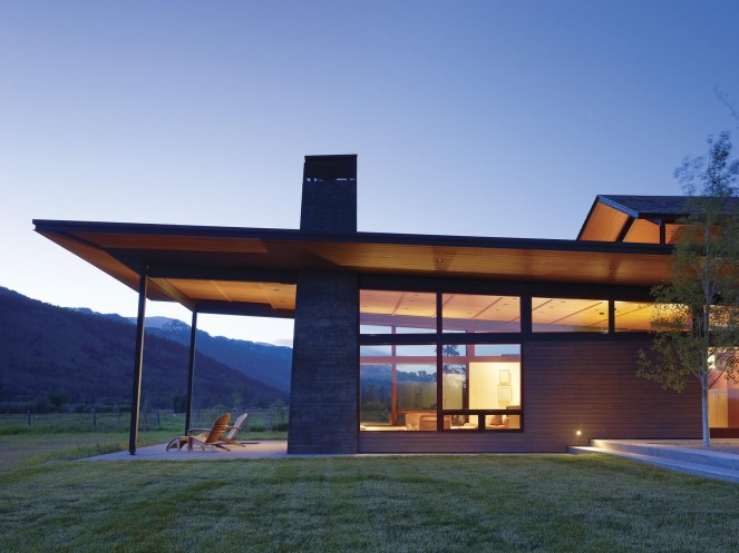 """with its expansive shed roof, tilts up to recognize views and capture daylight for the primary living spaces. Broad overhangs, articulated in wood, taper to a thin steel """"brim"""" that protects the buildings from harsh western weather."""