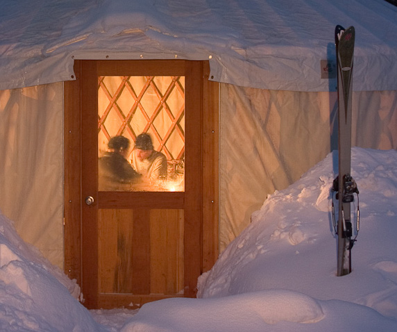 The warm glow of a backcountry ski yurt at dusk.