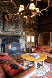 """Rustic elegance defines the Brooks Lake Lodge """"tearoom,"""" where a fire burns regularly in a massive stone fireplace and classic wildlife mounts adorn the walls."""
