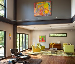 Throughout the home, stark lines and structural elements are highlighted by bold, fun colors and modern art. Here, the living room gets plenty of western light through a Vista wall, which can be fully opened.