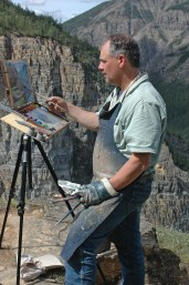 """Dwayne Harty painting en plein air overlooking the Nahanni River and Pulpit Rock, Nahanni National Park, Northwest Territories. """"In the three years traveling the Y2Y (Yellowstone to Yukon) mountain corridor I completed 110 plein air paintings as color reference preparatory to completing the larger easel paintings,"""" Hardy said."""