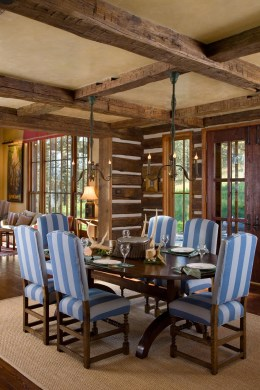 The blue and white striped upholstered chairs, coupled with a custom-designed trestle table add a pop of formality to balance the rustic elements of the architecture.