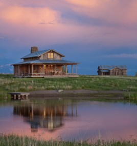 A low-hanging wrap around porch that overlooks a pond extends living space to the outdoors and connects this family camp in Montana's Shields Valley to the surrounding landscape.