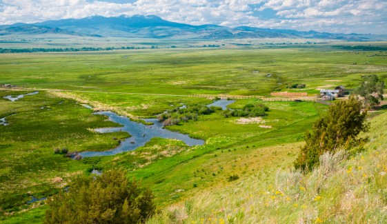 At the edge of a dry, wind-swept plateau, the land drops sharply revealing a lush wetland area.