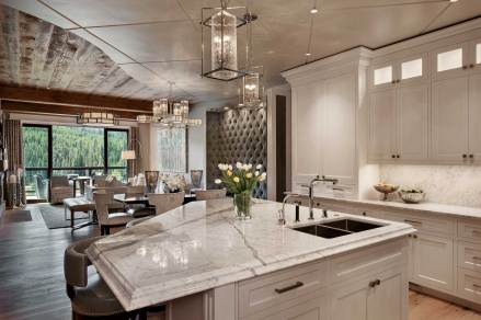 In the kitchen, the warm white of Italian marble countertops and custom white cabinetry by Mountain High Woodworks lend a contemporary flavor to the condo. An asymmetrical floating island divides the kitchen from the dining area.