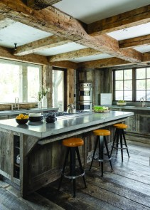 A marriage of rough and refined, weathered and reclaimed wood complements sleek concrete countertops and stainless steel appliances.