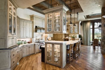 In the kitchen, the interior designer put a twist on the traditional form of the cabinetry, applying a distressed finish, but also by suspending two glass cabinets from the soffited ceiling with iron rods as a nod toward the rustic architectural elements of the home. A stainless steel hood over the stove is also strapped with iron to echo the rustic ties. The countertops are boutique quartzite and the flooring throughout the house is oak.