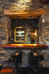 The tower serves four functions, one of which is as a bar, accessible from the living room. Reclaimed tactile materials and elaborate stonework provide a tie to history to achieve a classic old West feel that is also upscale and comfortable.