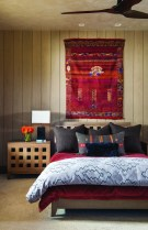"""In the bedroom, bright reds compliment the softer cream, gray and taupe tones. """"They wanted it to be comfortable and livable, to meet the Montana rustic aspects [of design] but also follow the clean and simple lines of contemporary interiors,"""" Elizabeth Schultz, interior designer, said."""