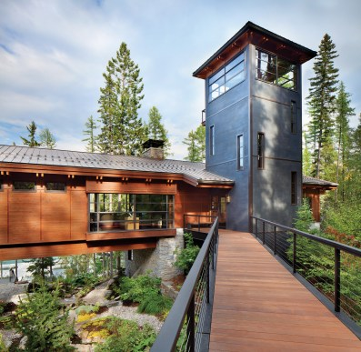 Guests enter the home via a new steel suspension bridge offset by a striking vertical tower skinned with a steel metallic plaster.