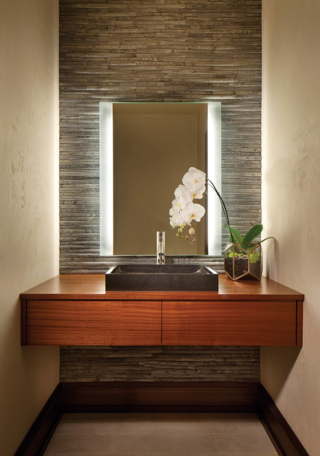 Venetian plaster, cut stone and Sapele hardwoods were used to create a dramatic effect in the guest bathroom.