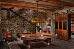 Utilizing multiple levels on the vertical-tiered site, a game room on the ground floor is ensconced in stone, wood and iron.
