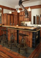 Reclaimed tractor seats become bar stools, and a welder's hood is repurposed as a kitchen vent.