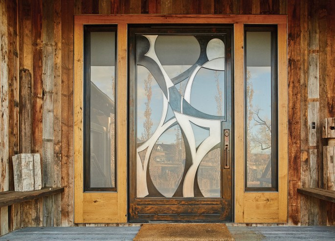 Glass and steel lend an industrial, edgy feel to the home, while the Picasso-esque, 700-pound pivot door provides a unique entry point. Reclaimed materials — such as barnwood and scrap metal — play a key role, as do hardwoods such as walnut and mahogany.