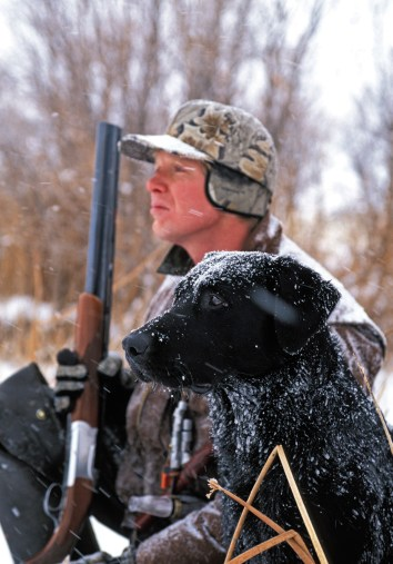 Duck hunter Marc Pierce and his lab, Chance, patiently await new arrivals to their decoy spread.