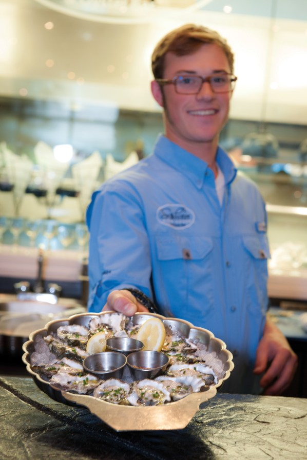 Danner is both bartender and master shucker, serving up smiles and seafare.