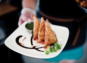 Traditional crispy samosas at Saffron Table are served with a contemporary presentation of mint chutney and garam masala.