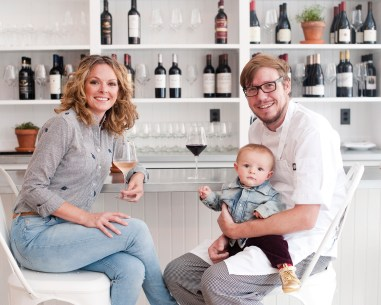 Owners Gena Burghoff and chef Chris Lockhart sit with baby Saxon at the bar of Ox Pasture. The couple brings a friendly, farm-to-table mission to their seasonal restaurant.