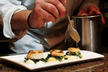 Chef Jake puts the finishing touches on a scallop starter. Photography courtesy Triple Creek Ranch