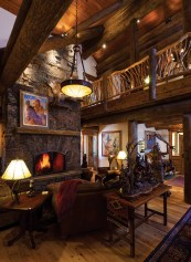 The living room reflects the Fuller's park architecture aesthetic with round log beams, organic branched railing and stacked stone fireplace.