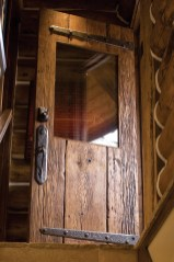 Decorative iron hinges and door pulls crafted by Gilmore complement the warm wood.