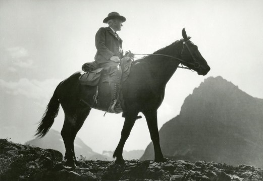 Stephen Mather on horseback in the Many Glacier Valley, Mount Gould and Grinnell Point in the background, 1926. Photo courtesy of Glacier National Park Archives