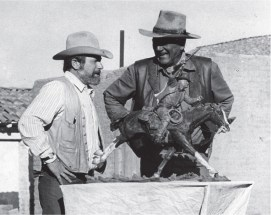 "The artist and John Wayne with the bronze of the actor's ""True Grit"" film character, Rooster Cogburn."
