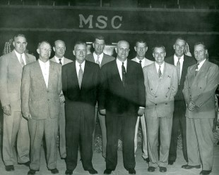Former players Brick Breeden, Cat Thompson, Max Worthington, Valery Glynn, Unknown, Harold Sadler, Frank Ward and Orland Ward, plus Coach Schubert Dyche (middle, left) honor their mentor, G. Ott Romney (middle, right) in 1953 when the College awarded him an honorary doctorate of Letters. Photo Courtesy of Gallatin History Museum – Bozeman, MT