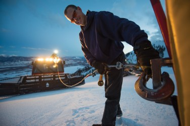 Justin Ellis hooks up his winch cat before grooming a steep slope.