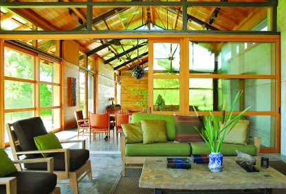"The home's design incorporates steel, concrete, Douglas fir and reclaimed barn wood. Sliding glass doors separate the enclosed porch (foreground) from the dining area. This ""public"" portion of the home can open to the outdoors with a series of pocketing glass doors."