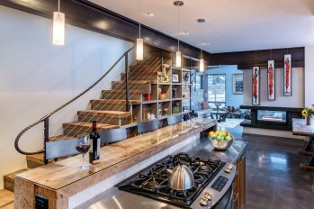 The clean lines of the open floor plan are accentuated by the railing of the floating staircase, made from a repurposed ski cable.