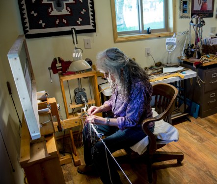 """Shoni works on a piece while sitting at her custom hitching jig. Ron is inventive, and designed the custom jig to suit Shoni's work. """"That is the beauty of being married to Ron,"""" Shoni jokes."""