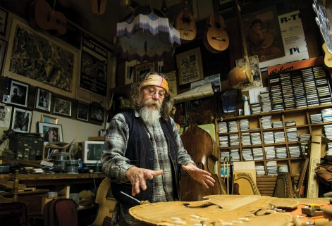 "Peter works on restoring a bass guitar in his workshop. ""It's like a museum in here,"" he says. He has all kinds of rebuilding, restoring, and repair projects at various stages."